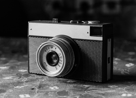 bedspread: old scratched vintage camera lying on the old bedspread