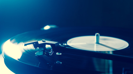 Vintage record player with vinyl disc, close-up. blue lighting