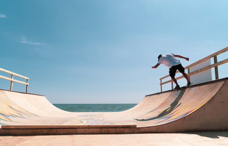 the guy skates on a ramp for tricks. by the sea