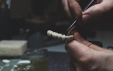 A dental technician makes a prosthetic teeth. laboratory. close-up