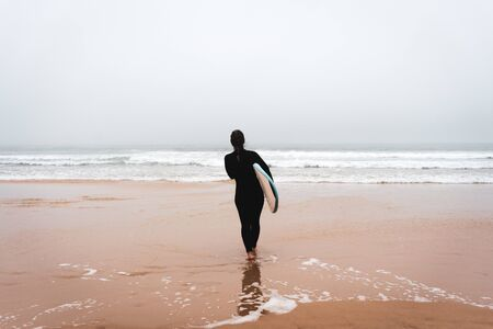 Young girl server stands with a surfboard by the ocean. stormy weather. 写真素材