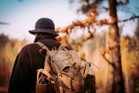 young guy with a vintage backpack in the forest
