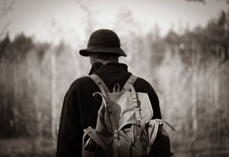 young guy with a vintage backpack in the forest. black and white