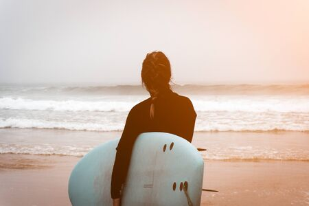 Young girl server stands with a surfboard by the ocean.