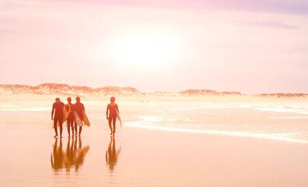 A group of surfers walks along the ocean beach. sunny 写真素材