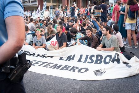 Peace protest in Lisbon, Portugal on October 5, 2019. Protesters are sitting with posters near the police.
