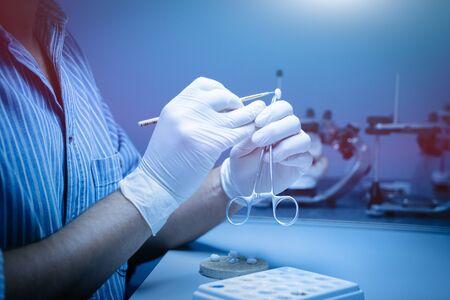 A dental technician makes a dental crown. laboratory. close-up