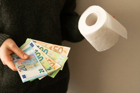 girl holds euro banknotes and toilet roll 写真素材