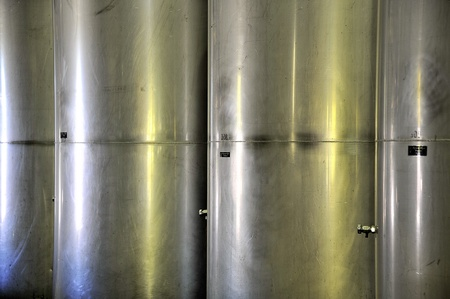row of four stainless steel wine tanks photo