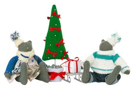 Two stuffed cat toys in pants and dress sitting with fir tree and sled with gift box nearby. Decoration for Christmas. Isolated on white. photo