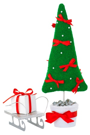 Stuffed green fir tree toy decorated with red bows and white beads in a white flowerpot with white decorated gift box on a sled aside. Decoration for Christmas. Isolated on white. photo