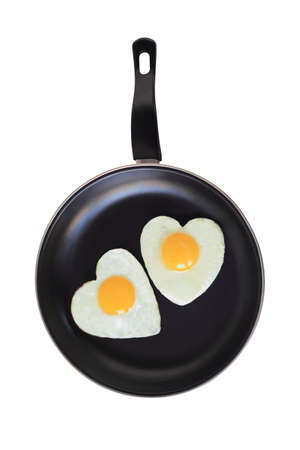 fried eggs as hearts on a frying pan