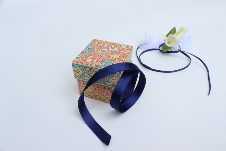 image of closed gift box with blue ribbon and decorative flowers photo