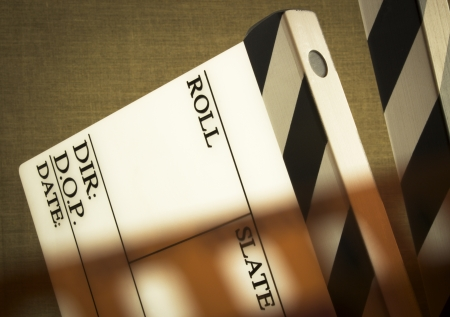 fine image of clapboard with film tape on brown background photo