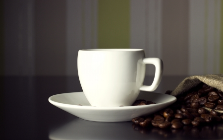 white cup with coffee beans on black table photo