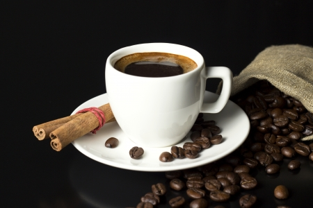 coffee cup with fresh roasted beans and vintage sack on black table photo
