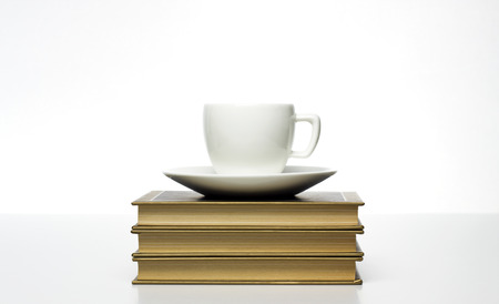 white cup on vintage books photo