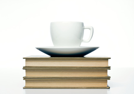 cup with books on white background photo