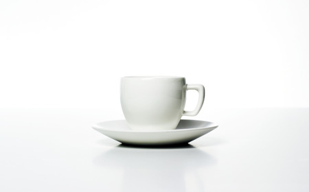 white cup with saucer on morning table