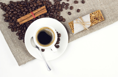 coffee cup with beans and cereal snack on white table photo