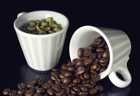 striped cups with green and roasted coffee beans