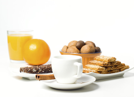 coffee cup with cookies nuts and orange juice on white