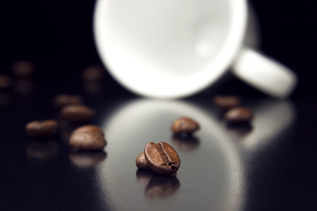 natural coffee beans with white cup on table photo