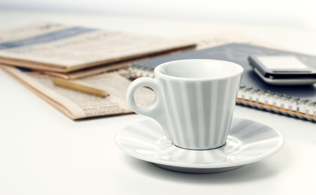 coffee cup notebook with newspapers on white desk photo