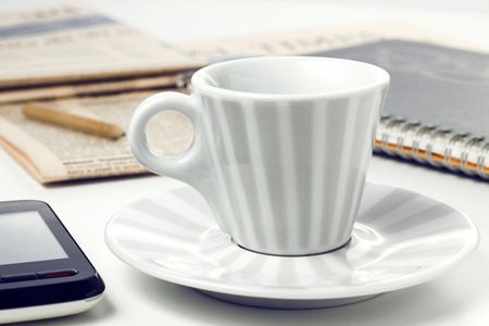 smart phone and coffee cup  on white desk photo
