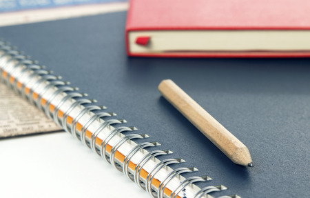 notepads with wooden pencil and newspaper on desk photo