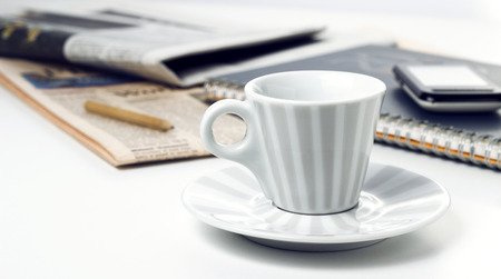 retro style coffee cup with notepad phone and newspapers on office desk photo