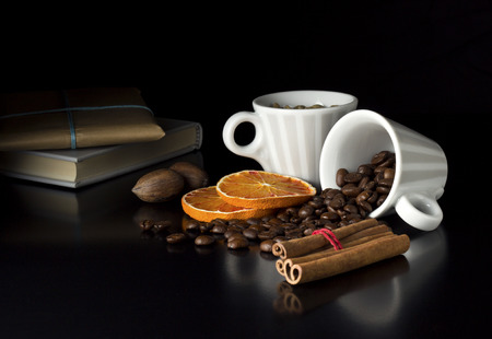 roasted coffee beans with fruits book and gift on black table photo
