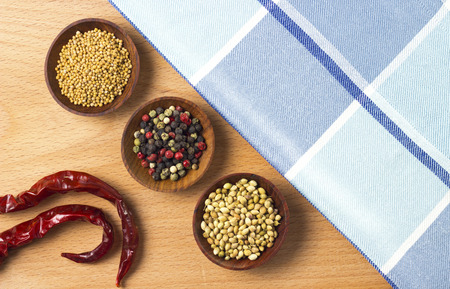 colorful spices and chili peppers on wooden table photo
