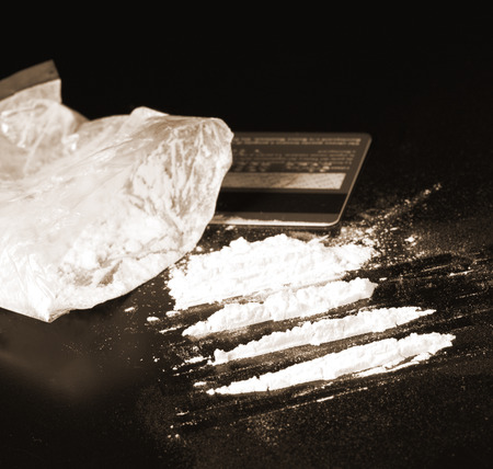 cocaine portions on black table and bank card
