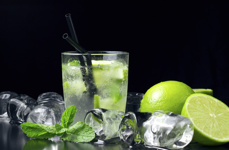 Mojito cocktail with fresh limes, mint and ice cubes on black table photo