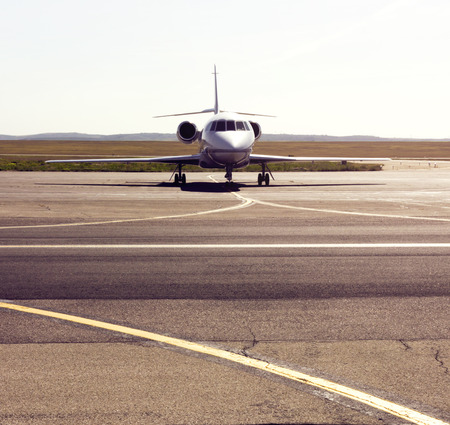 airport runway: parked private airplane on the runway. white civic jet Stock Photo