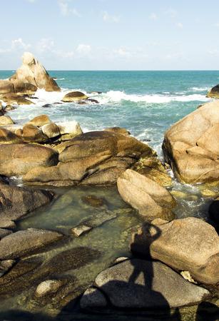 sea waves: beautiful view of coastline rocks, sea waves and photographer silhouette. summer tour adventure Stock Photo