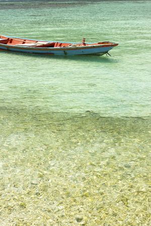 shallop: old wooden boat near peaceful, tropical beach. summer holidays background