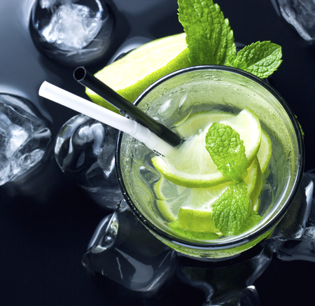 cold Mojito cocktail with fresh lime, mint and ice on black table