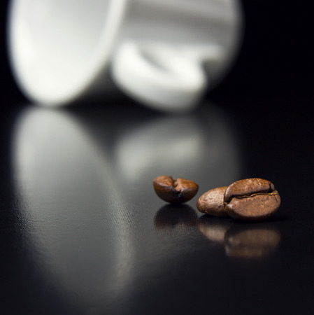 coffee beans with white cup on black table. creative product presentation background
