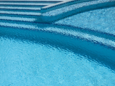 Turquoise swimming pool with steps, dark blue trim and rippling water.