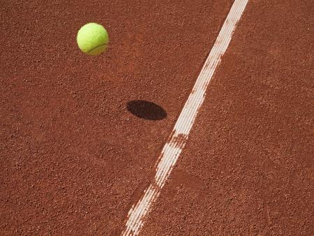テニスボール空気赤粘土裁判所ラインに近づいています。 写真素材