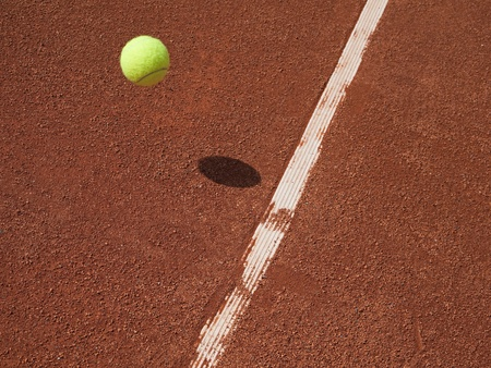 Tennis ball in air approaching the line on a red clay court.