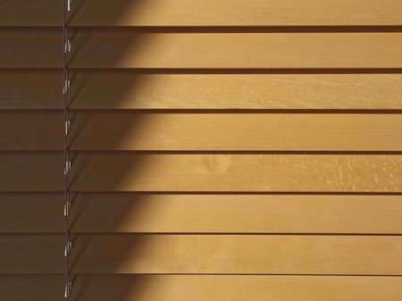 beneath: Beechwood blinds in sunlight. Shadow and adjustment string on the left with diminishings shadows beneath the shutter strips.