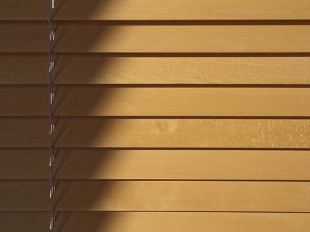 Beechwood persiane alla luce del sole. Strisce di ombra e cordino di regolazione a sinistra con diminishings ombre sotto il pulsante di scatto. Archivio Fotografico - 9796778