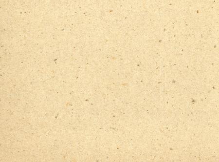 Le particelle di carta riutilizzata formano una texture su questo sfondo color crema.