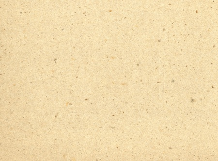 Particles of reused paper form a texture on this cream colored background. Standard-Bild