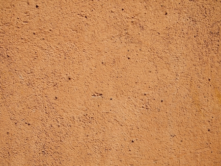 明るい日光の下でのテラコッタ オレンジ セメントまたは化粧漆喰の壁。