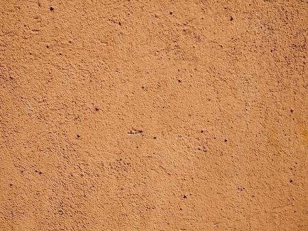 Terra cotta orange cement or stucco wall in bright sunlight.