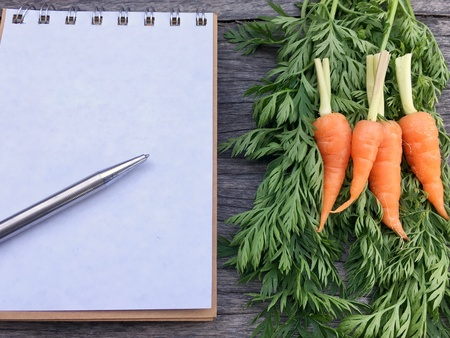 Orange baby carrot put beside notebook and pen. Stock Photo